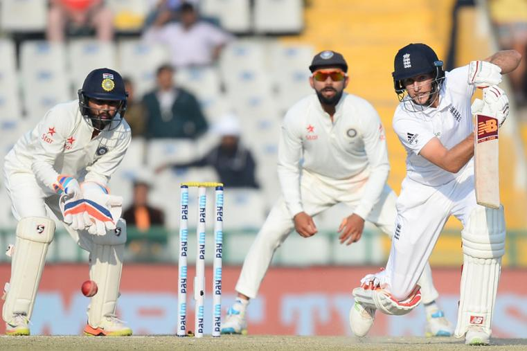 England batsman Joe Root plays a shot as Indian captain Virat Kohli  (C) and wicketkeeper Parthiv Patel look on during the third day of the Mohali Test. (AFP Images)