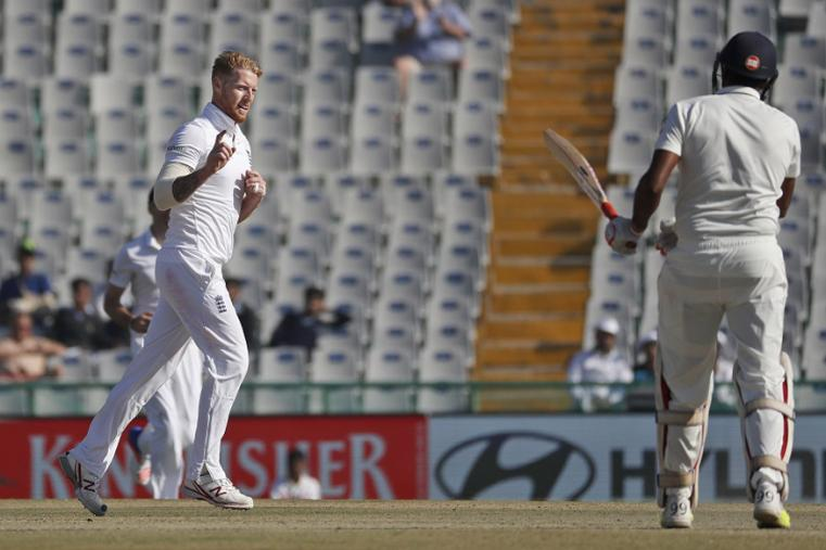 England's Ben Stokes, left, celebrates after taking the wicket of India's Ravichandran Ashwin, right, on the third day of the Mohali Test. (AP Images)