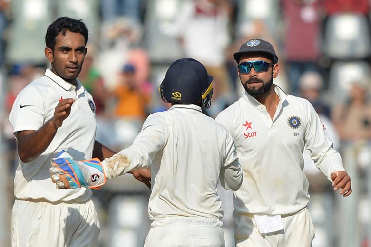 Jayant Yadav celebrates the wicket of Joe Root with Virat Kohli and Parthiv Patel during the fourth day of the fourth Test between India and England at the Wankhede. (AFP Images)