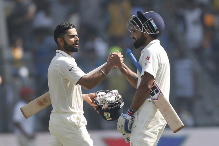 Indian cricket captain Virat Kohli, left, greets Murali Vijay during the third day of the fourth Test between India and England at Wankhede. (AP Images)