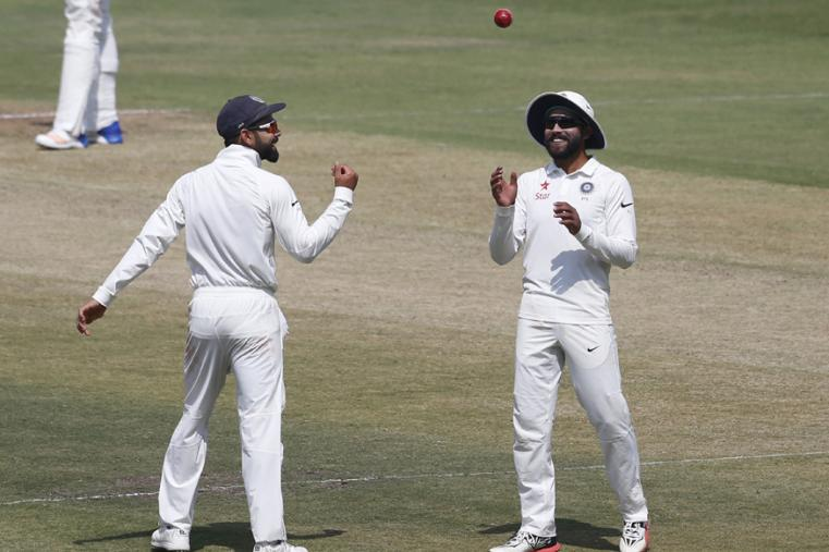 Virat Kohli, left, throws the ball to Ravindra Jadeja during the last day of the one-off cricket test match against Bangladesh in Hyderabad. (AP Photo)
