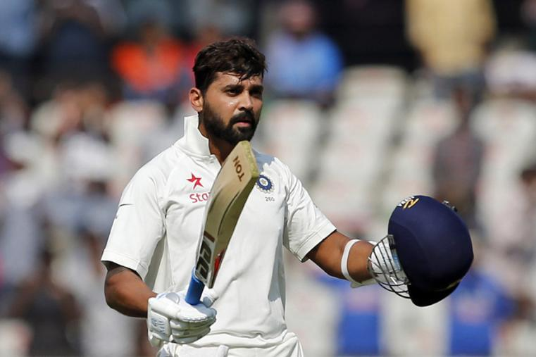 India's Murali Vijay raises his bat and helmet to celebrate his century on the first day of the Hyderabad Test. (AP Photo)