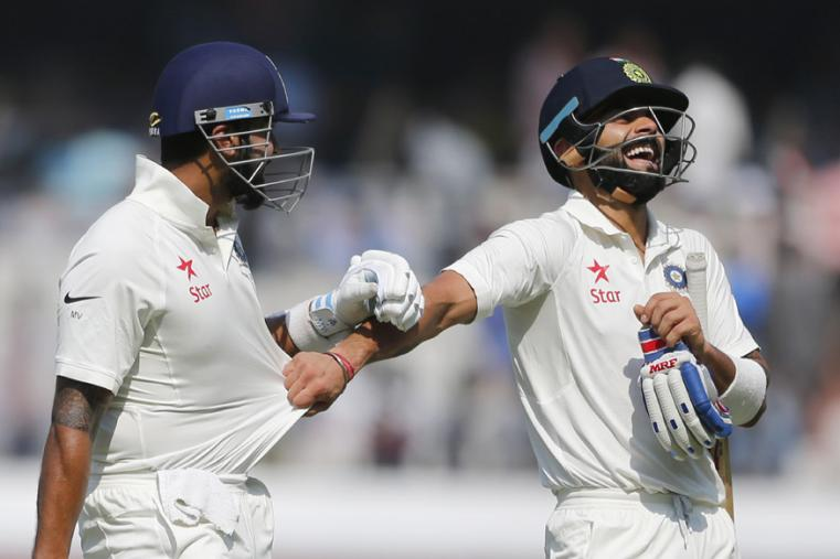 India's captain Virat Kohli, right, pulls the shirt of teammate Murali Vijay as they leave the ground for tea break during the first day of the Hyderabad Test. (AP Photo)