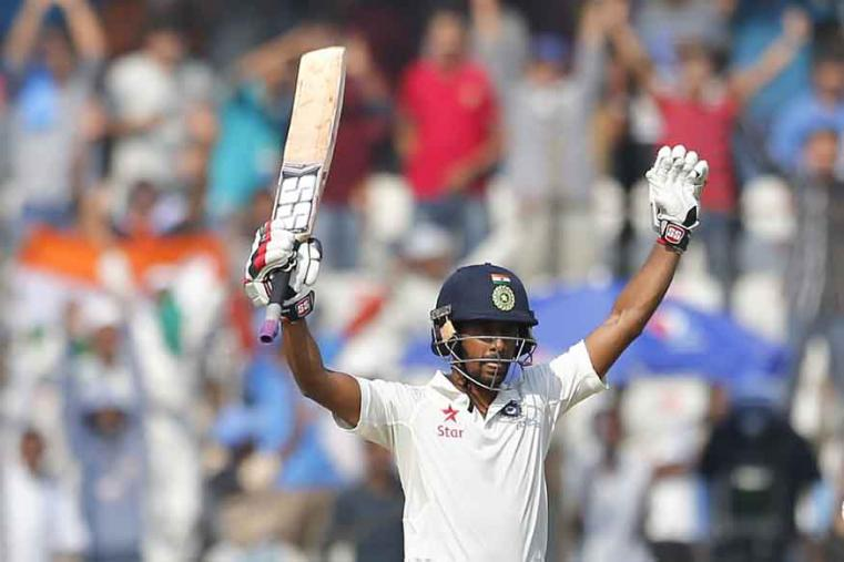 India's Wriddhiman Saha raises his bat to celebrate scoring a century during the second day of the only Test between India and Bangladesh. (AP Photo)
