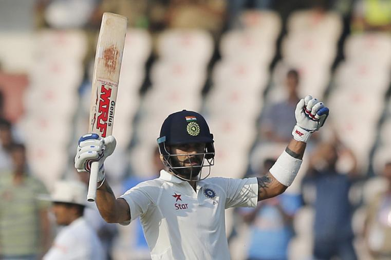 India's captain Virat Kohli raises his bat to celebrate his 16th Test century on the first day of the Hyderabad Test. (AP Photo)