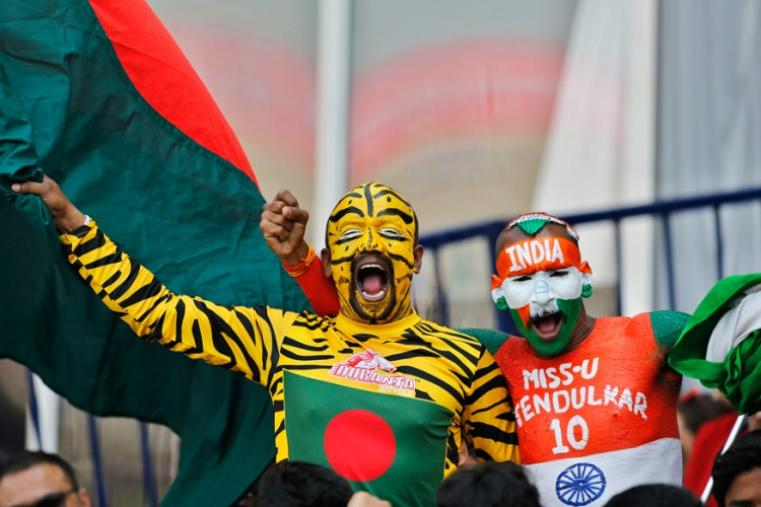 India and Bangladesh cricket fans with faces painted in the colors of their national flags cheer for their teams. (AP Photo)
