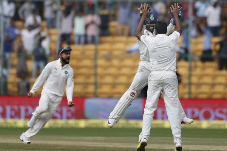 India's Ravichandran Ashwin, back to camera, celebrates with teammate Wriddhiman Saha after their win over Australia on the fourth day of the Bengaluru Test. (AP Photo)