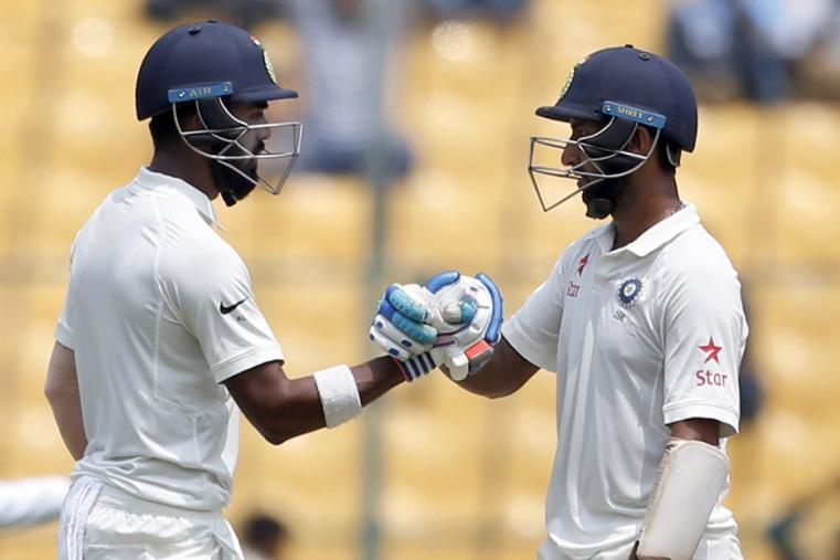 India's Cheteshwar Pujara, right, congratulates teammate Lokesh Rahul on scoring fifty runs during the third day of the Bengaluru Test. (AP Photo)