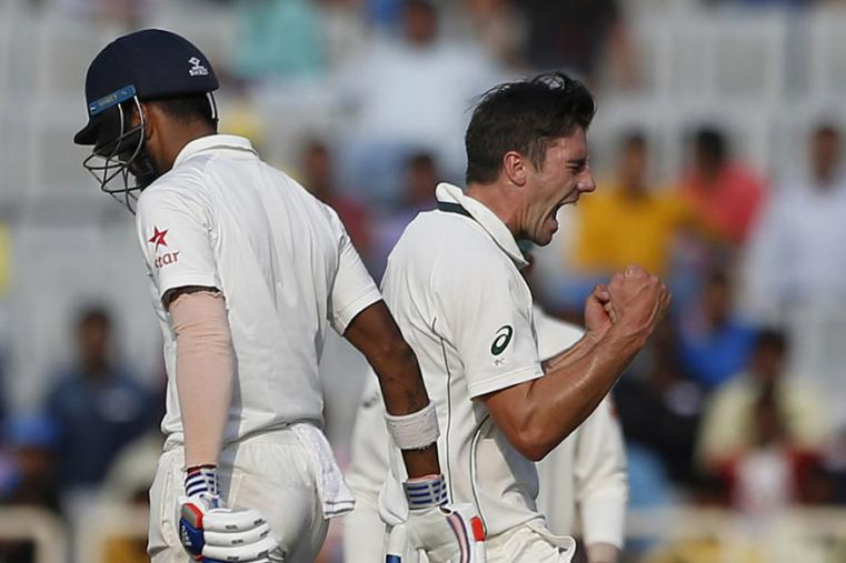 Australia's Pat Cummins, right, celebrates the dismissal of India's Lokesh Rahul, left, during the second day of the Ranchi Test. (AP Photo)