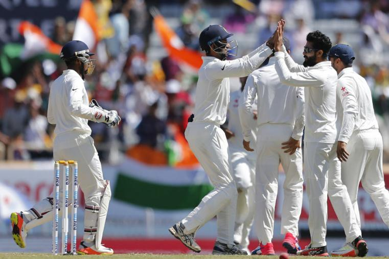 India's Ravindra Jadeja, second right, celebrates with teammates the dismissal of Australia's David Warner during the first day of the Ranchi Test. (Ap Photo)