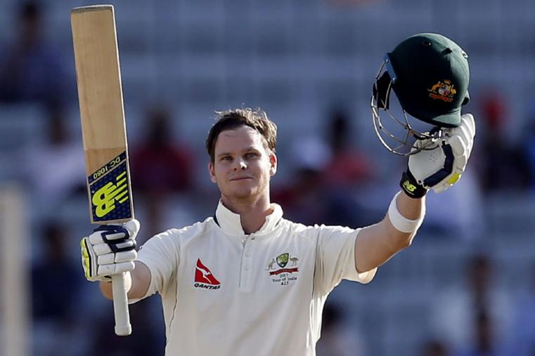 Australia's captain Steven Smith raises his bat and helmet to celebrate scoring a century during the first day of the Ranchi Test. (Ap Photo)