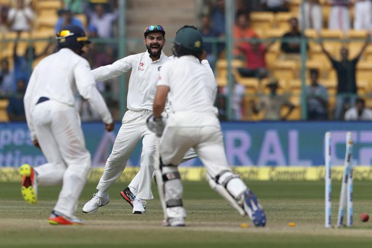 India's captain Virat Kohli, center, celebrates the dismissal of Australia's Steve O'Keefe, right, during the fourth day of the Bengaluru Test. (AP Photo)