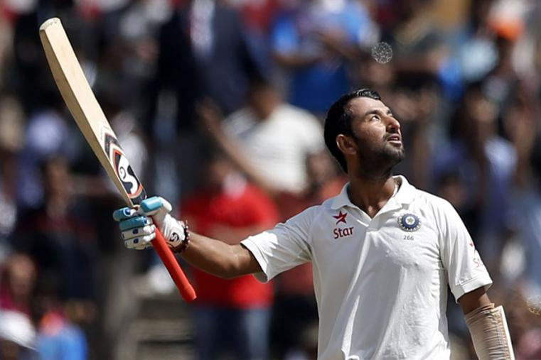 India's Cheteshwar Pujara looks skywards and raises his bat to celebrate scoring a century during the third day of the Ranchi Test. (AP Photo)