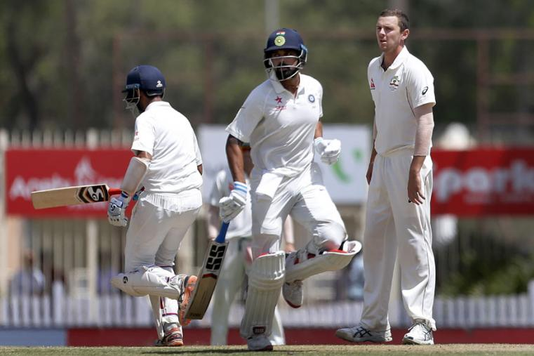 Australia's Josh Hazlewood, right, reacts as India's Murali Vijay, center, and Cheteshwar Pujara, left, run between the wickets during the third day of the Ranchi Test. (AP Photo)